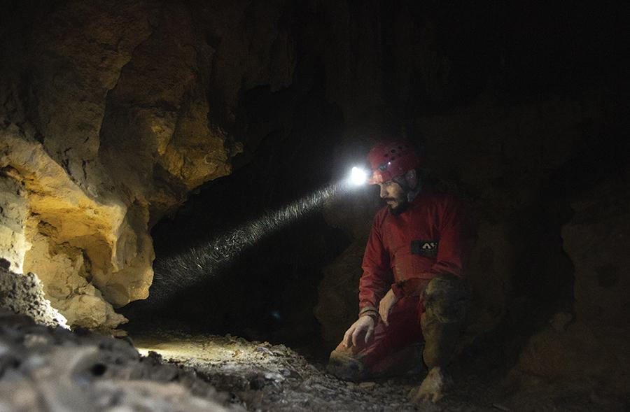 Ionuț Mirea în Peștera Muierilor uităndu-se la fosile de urși de peșteră